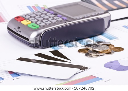 Business still-life of a payment terminal, cards, money, coins