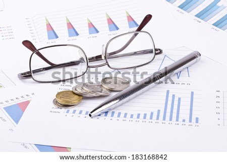 Business still-life of a pen, diagram, eyeglasses, coins
