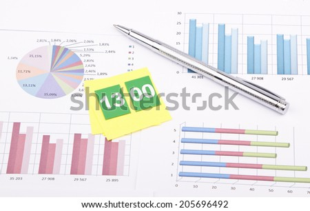 Business still-life of a pen, sticker, numbers, graphs - stock photo