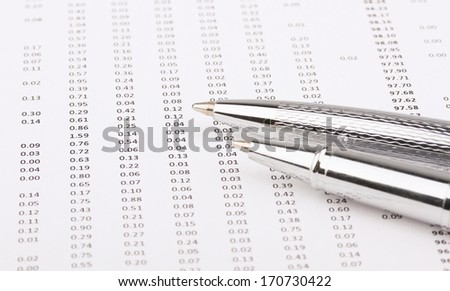 Business still-life of a two shine pen, charts.