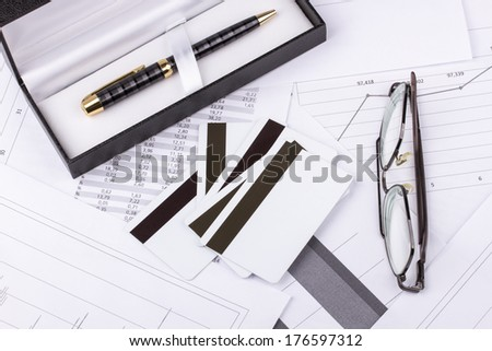 Business still-life of pen, charts, tables, eyeglasses, credit Cards