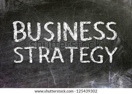 Business strategy handwritten with white chalk on a blackboard. - stock photo