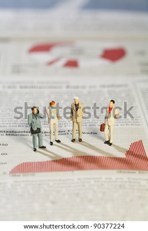 Business Strategy Meeting, four miniature models of businessmen standing above a bar graph as though in a meeting. - stock photo