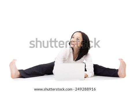 Business, study, healthy lifestyle. Smiling young female office employee in formal wear doing splits, sitting in yoga pose in front of silver laptop with dreamy look, isolated on white background