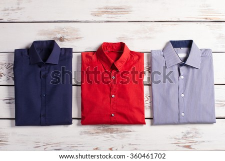 Business stylish men's shirts with different colors and prints on wooden background. - stock photo