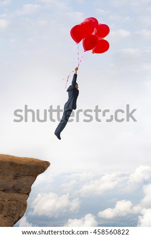 business success concept businessman flying upward with helium balloons