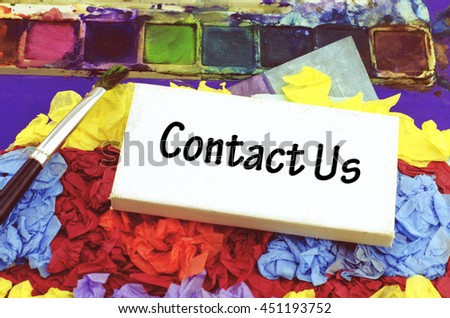 Business success word concept with word contact us over small white canvas frame on crumple texture color paper, paint brush and water color on tray - stock photo