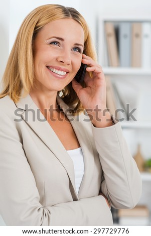 Business talk. Beautiful mature businesswoman talking on the mobile phone and smiling