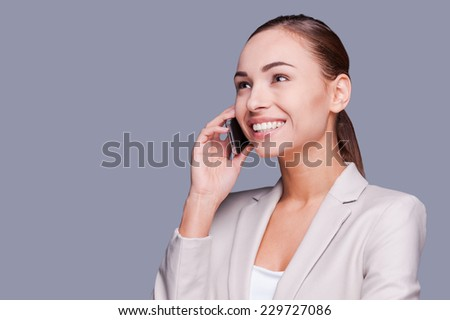 Business talk. Beautiful young businesswoman talking on the mobile phone and smiling while standing against grey background - stock photo