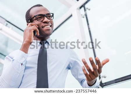 Business talk. Low angle view of confident young African man in shirt and tie talking on the mobile phone and gesturing - stock photo