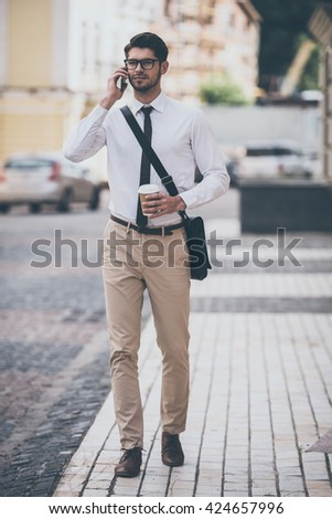 Business talk on a go. Full length of confident young man in glasses holding coffee cup and talking on mobile phone while walking outdoors  - stock photo