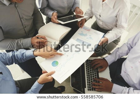 Business team analyzing and discussing charts, view from above