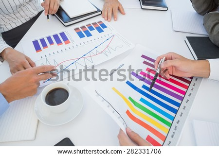 Business team analyzing bar chart graphs in the office