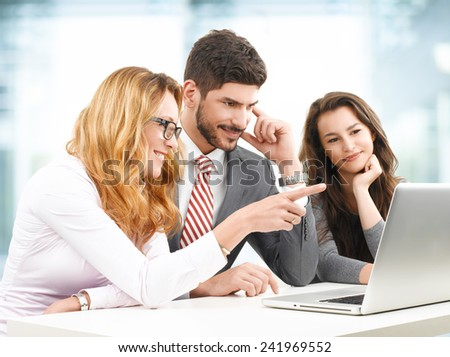 Business team analyzing financial data on laptop while sitting at office.  - stock photo