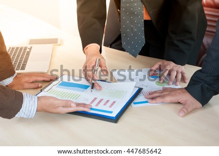 Business team analyzing financial documents in office - stock photo