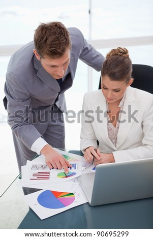 Business team analyzing survey results together - stock photo