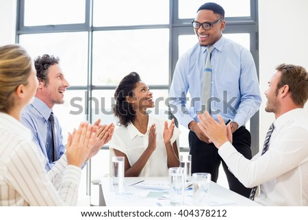 Business team applauding a colleague in meeting - stock photo