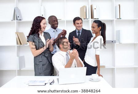 Business team applauding a female colleague for her ideas in office - stock photo