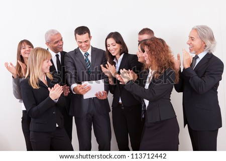 Business Team Applauding For The Success Of Colleague - stock photo