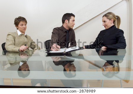 Business team at desk with one associate looking upset at others flirting.