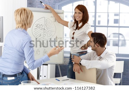 Business team at presentation, businesswoman drawing diagram on whiteboard, smiling. - stock photo