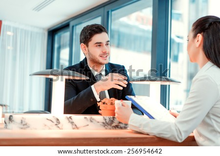 Business team at the meeting. Handsome young man speaking with his female colleague while sitting at the restaurant - stock photo