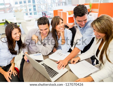Business team at the office working on a laptop - stock photo