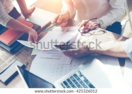 Business team brainstorming. Marketing plan researching. Paperwork on the table, laptop and mobile phone - stock photo