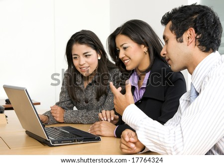 business team browsing on a laptop - smiling over a white background - stock photo