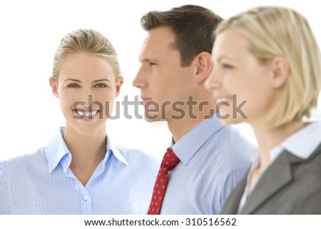 Business Team. Business people standing in a row. Selective focus on the woman looking at the camera in the background. Two others looking away. Profile view. - stock photo