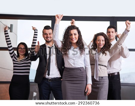 Business team celebrating a triumph with arms up in office