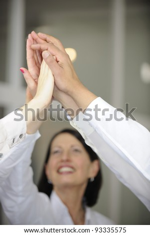 Business team celebrating success with high five, copyspace - stock photo