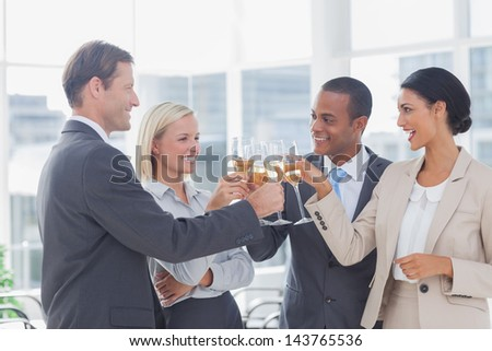 Business team celebrating with champagne and toasting in the office - stock photo