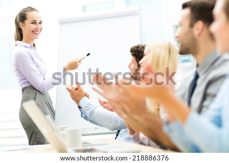 Business team clapping in meeting - stock photo