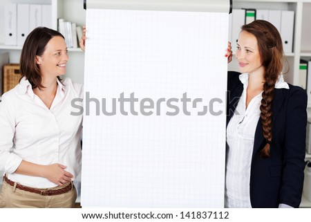 Business team consisting of two attractive smart young women standing on either side of a blank flip chart - stock photo