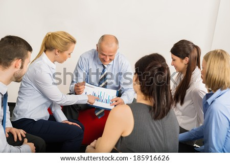 Business team discussing analysis graph sitting in meeting room - stock photo