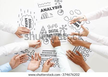 Business team discussing digital marketing ideas - stock photo