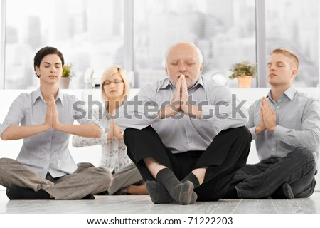 Business team doing yoga meditation wearing formal clothes, sitting on floor with eyes closed in office.? - stock photo
