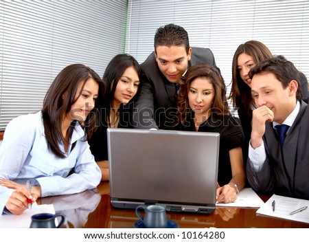 business team during a meeting in an office looking at a laptop computer - stock photo