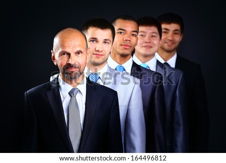 Business team formed of young businessmen and the leader standing over a dark background - stock photo