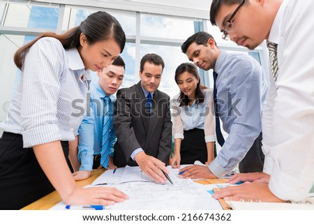Business team gathered around table to discuss new strategy - stock photo