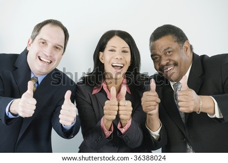 Business team giving thumbs up sign - stock photo
