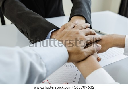 Business team hands on meeting desk - stock photo