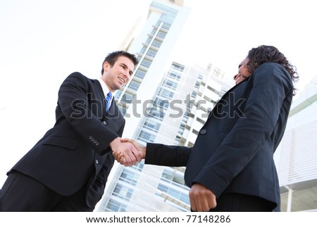 Business team handshake between man and woman of different ethnicities - stock photo