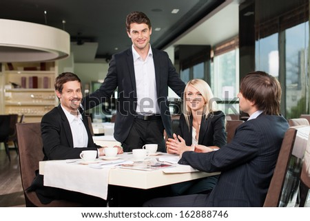 Business team having meeting at the restaurant. One man standing  - stock photo