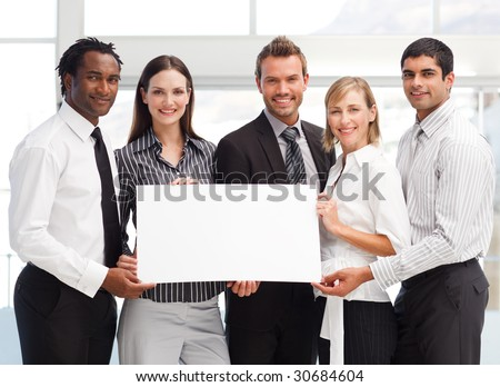 Business team holding a blank card in front of the camera - stock photo
