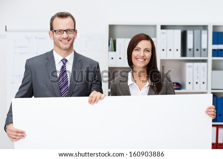 Business team holding a blank white sign with a smiling successful man and woman standing side by side in the office with the sign in front of them with copyspace for your text or advertisement - stock photo