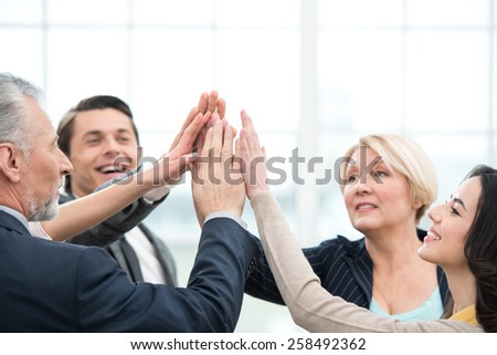 Business team holding hands to hands. Office interior with big window