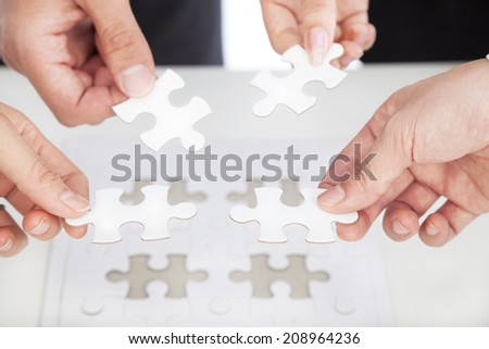 Business team Holding Jigsaw Puzzle on the desk - stock photo