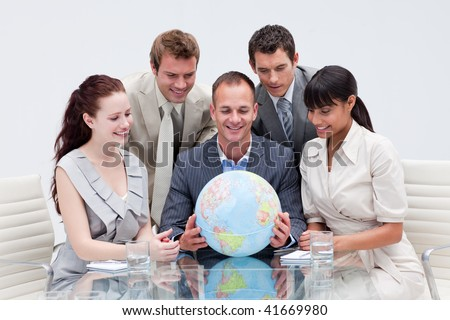 Business team holding the world in the office. Global expansion - stock photo